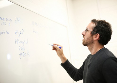 Justin Boutilier writing a formula on a whiteboard