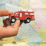 A toy ambulance being held in front of a map of Dhaka, Bangladesh