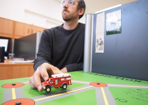 Researcher Justin with a toy ambulance
