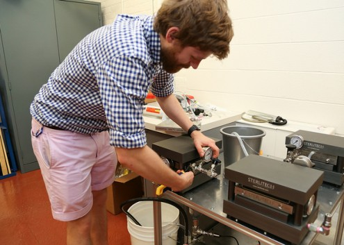 Researcher adjusting water testing instrument